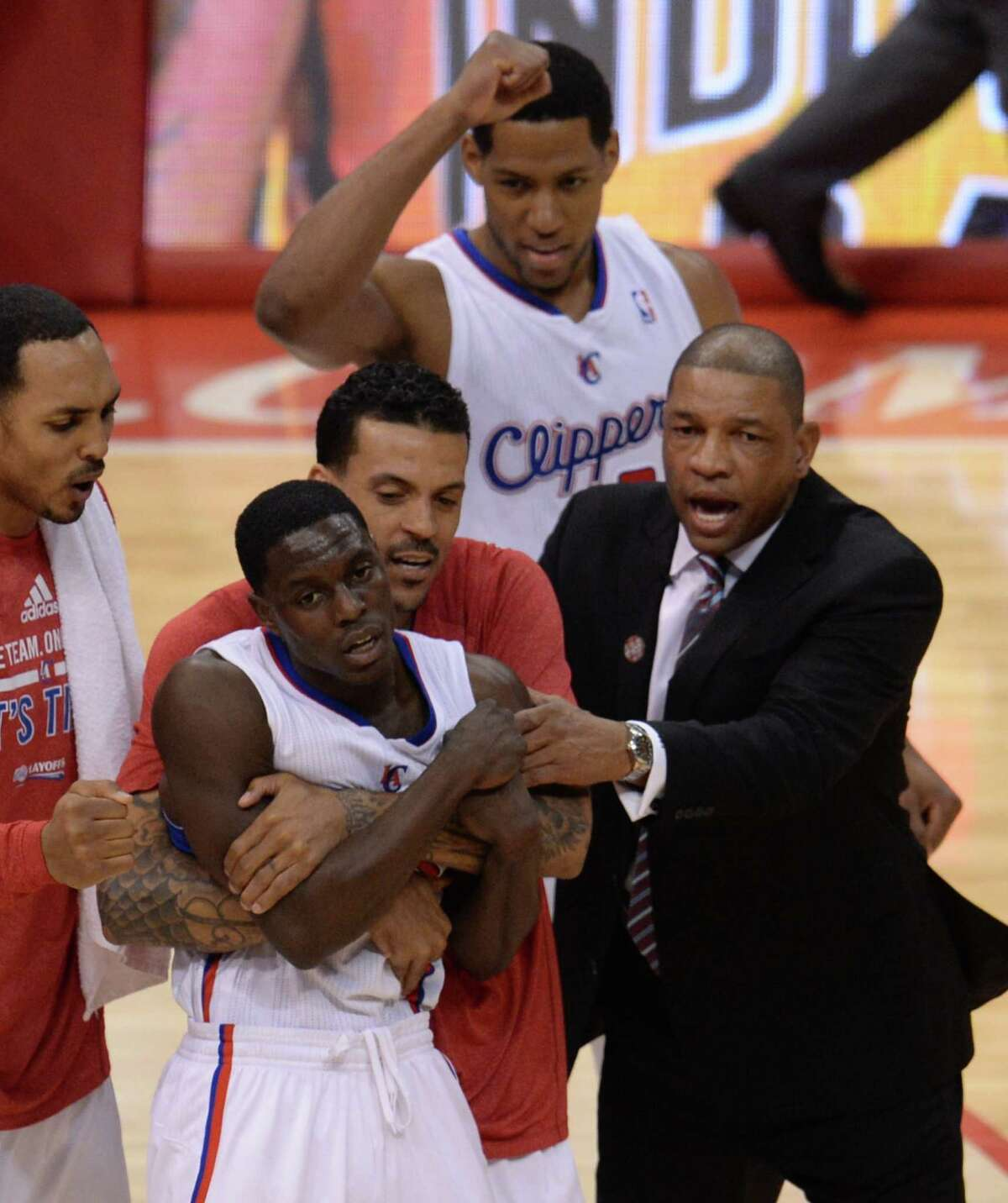 After coming up big down the stretch in Sunday's win over the Thunder, Darren Collison, center, gets mobbed by his Clippers teammates and coach Doc Rivers.
