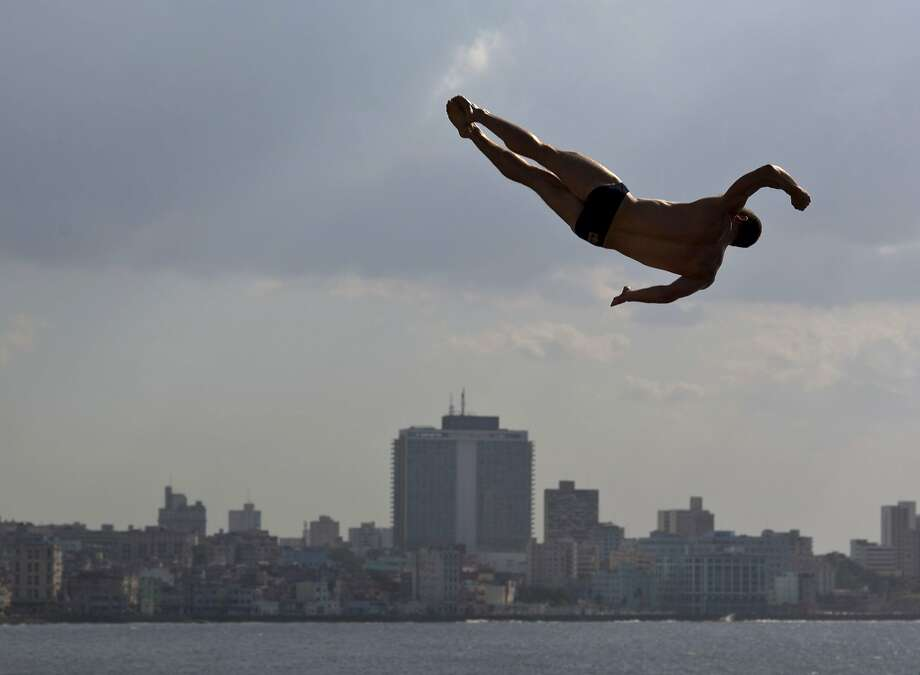 An athlete dives from the Red Bull Cliff Diving World Series platform in the final round, in Havana, Cuba, Saturday, May 10, 2014. The world's best cliff divers jumped from the 27-meter platform positioned on the historic Morro Castle in Havana.  (AP Photo/Ramon Espinosa) Photo: Ramon Espinosa, Associated Press
