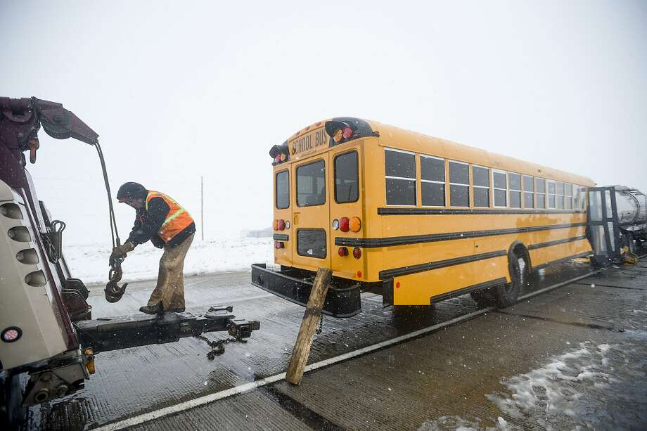 Crews clean up a school bus and semi collision on northbound I-25 Sunday, May 11, 2014 in Fort Collins, Colorado. The driver of the bus, who was the only occupant of the vehicle, was the only one injured in the crash. (AP Photo/The Coloradoan, Erin Hull) Photo: Erin Hull, Associated Press