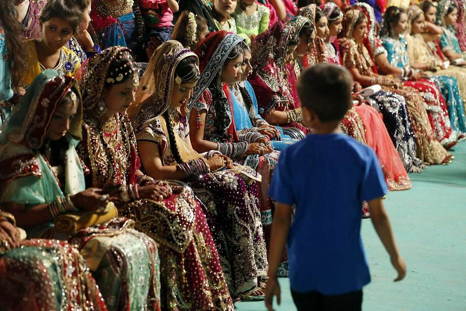 A boy walks past Indian Muslim brides sitting during a mass marriage where thirty-five couples got married in Mumbai, India, Sunday, May 11, 2014. (AP Photo/Rajanish Kakade) Photo: Rajanish Kakade, Associated Press