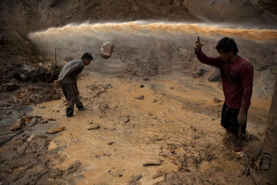 "In this May 3, 2014 photo, a jet stream of water passes above two miners known as ""Maraqueros"" who remove stones and chunks of tree trunks that have been released with the aid of a rustic type of hydraulic jet known locally as a ""Chupadera,"" in La Pampa in Peru's Madre de Dios region. The Chupadera aims powerful jet streams of water at earth walls, releasing the soils that hold the sought after flecks of gold. (AP Photo/Rodrigo Abd) Photo: Rodrigo Abd, Associated Press"