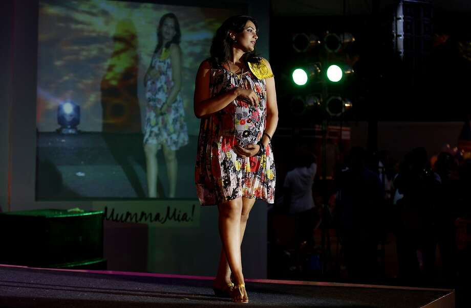 An expectant mother holds on to her belly as she pauses on the ramp during a fashion show organized to mark Mother's Day in Bangalore, India, Sunday, May 11, 2014. (AP Photo/Aijaz Rahi) Photo: Aijaz Rahi, Associated Press