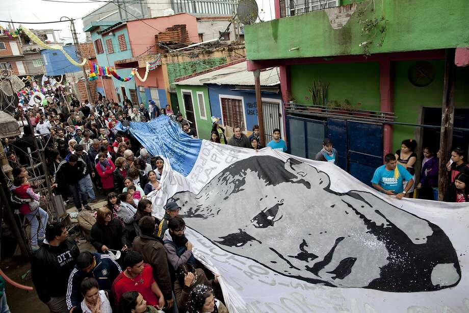 "A banner, with the face of priest Carlos Mugica is carried by marchers during a procession on the 40th anniversary of his assassination at the ""31"" slum in Buenos Aires, Argentina, Sunday, May 11, 2014. The religious leader, who is widely recognized as a father of social justice, was remembered with a mass, a festival and a procession inside the slum he used to preach, among other activities. He was assassinated in 1974 by the Argentine Anti-Communist Alliance when he had just finished celebrating a mass in Buenos Aires. (AP Photo/Natacha Pisarenko) Photo: Natacha Pisarenko, Associated Press"