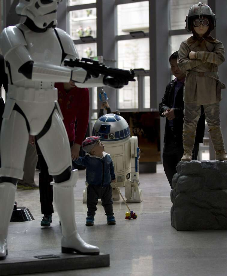 A child walks near the life-size characters figures of the Star Wars movies on display at a shopping mall in Beijing, China Sunday, May 11, 2014. (AP Photo/Andy Wong) Photo: Andy Wong, Associated Press