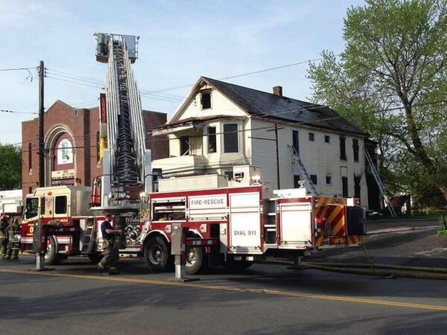 Firefighters remain at the scene in the aftermath of a fire that damaged a building at 820 State St., Schenectady on Monday, May 12, 2014. (Skip Dickstein / Times Union)