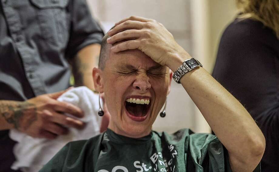 All gone:Jamie Powell reaches for her missing hair after being shaved at a St. Baldrick's 