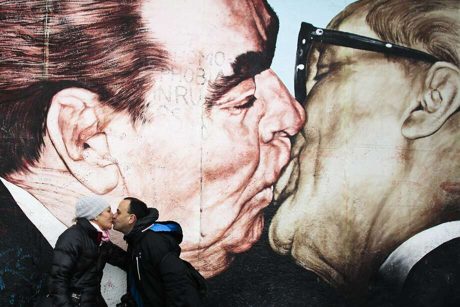 Kiss off, Soviet Bloc heads! A Mexican couple mimics a Dmitri Vrubel painting of former Soviet Leader Leonid Brezhnev and 