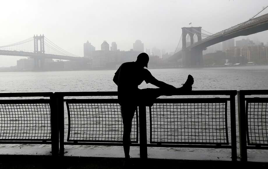 River run: Phil Holden stretches before resuming his jog along a foggy East River waterfront between the 