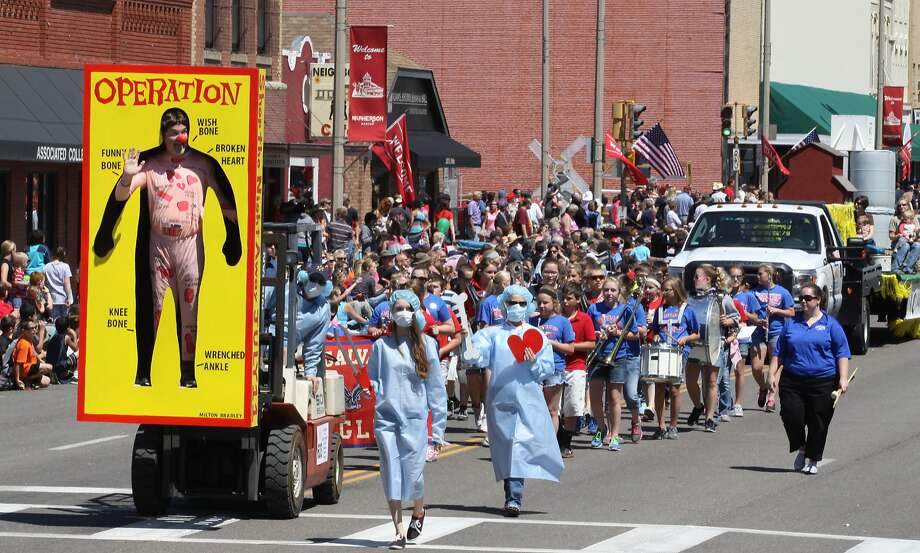 I owe it all to Obamacare: An obviously recovered Milton Bradley Operation board game patient waves to the crowd during the 101st Annual 
