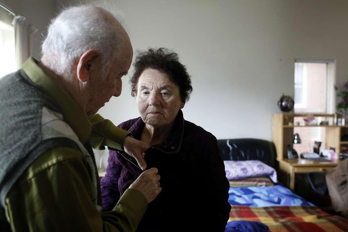 Roman Shatsov, 84 helps his wife Faina Burovaya with her coat as they prepare to take the bus to the Russian American Community Services for lunch, Tuesday April 15, 2014, in San Francisco, Calif.