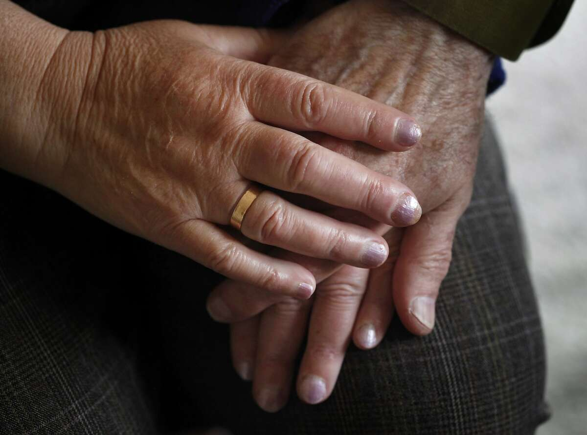 Roman Shatsov, 84 and his wife Faina Burovaya hold hands as they sit in their apartment, Tuesday April 15, 2014, in San Francisco, Calif. Shatsov and Burovaya have Alzheimer's and Parkinson's and are being threaten of eviction because they rent using section 8 vouchers.