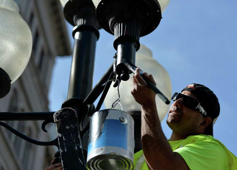 Department of General Services worker Miguel Lugo touches up the paint on the street lamps Monday morning, May 12, 2014, on Broadway in front of the Federal Courthouse in downtown Albany, N.Y. (Skip Dickstein / Times Union) Photo: SKIP DICKSTEIN