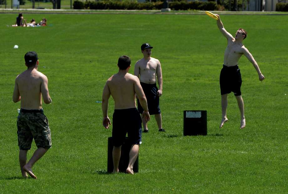 University at Albany students use the great weather to play Frisbee on the north side of the campus Monday afternoon May 12, 2014 in Albany N.Y.   The students from left to right are Joe Petrie 21, from Suffolk;  David Thomsen, 22, of Ryebrook;  Kevin Sawler, 19, of Yorktown and Jake Goldsmith, 20, of Suffolk.     (Skip Dickstein / Times Union) Photo: SKIP DICKSTEIN