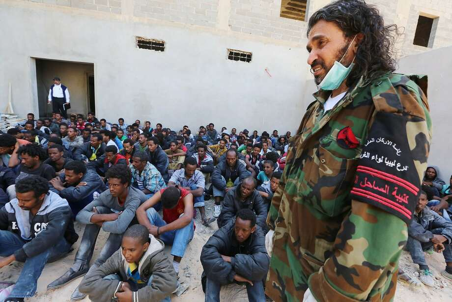 A member of the Libyan security forces stands guard near some 340 illegal migrants who were rescued by the Libyan navy off the coast of the western town of Sabratha when their boat began to take on water, on May 12, 2014. The rescue came on the same day Italy's navy said at least 14 migrants had died when their boat sank between Libya and Italy, the latest in a string of shipwreck tragedies to hit the Mediterranean. Libya has long been a springboard for Africans seeking a better life in Europe, and the number of illegal departures from its shores is rising.AFP PHOTO / MAHMUD TURKIAMAHMUD TURKIA/AFP/Getty Images Photo: Mahmud Turkia, AFP/Getty Images