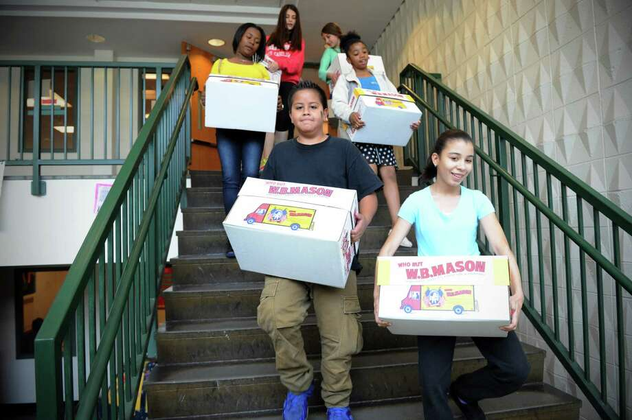 Rippowam Middle School students have collected nearly 2,500 books for Kids Helping Kids, a program that sends literature to overseas schools. They carry  the boxes of books on Monday May 12, 2014 in Stamford, Conn. Photo: Dru Nadler / Stamford Advocate Freelance