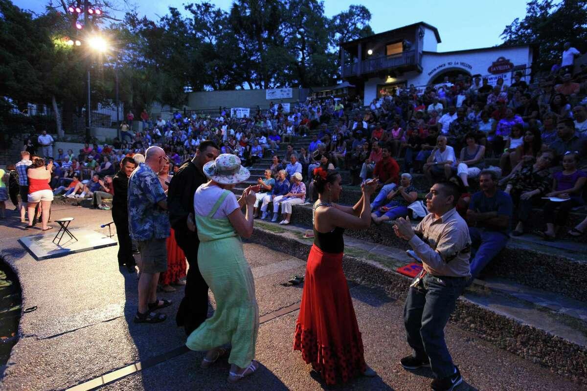 Audience members dance with Fiesta Noche del Rio dancers during the 57th season of Fiesta Noche del Rio Saturday July 6, 2013 at the Arneson River Theatre.