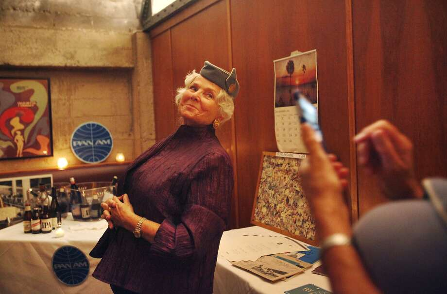 Former stewardess Kay Pritchard Oppenheimer, 71, wears a vintage Pan Am hat as Edith Kipping, 73, takes a photo. Photo: Leah Millis, San Francisco Chronicle