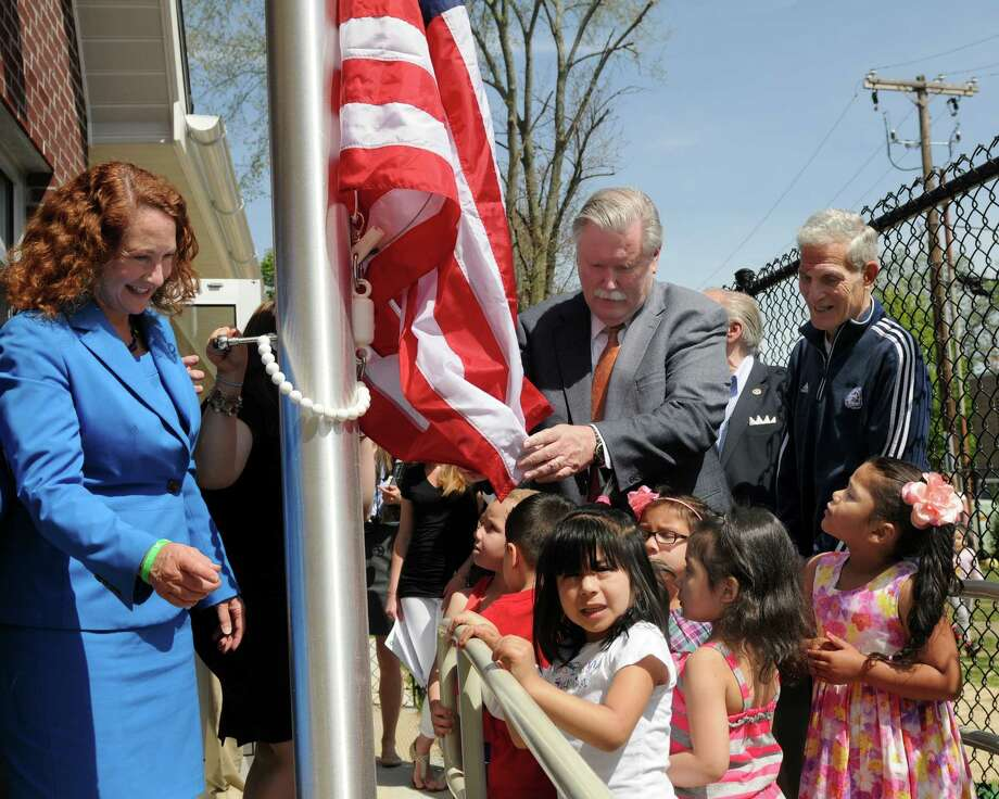 U. S. Rep. Elizabeth Esty, D, 5th,left, and James Maloney, president of Connecticut Institute for Communities, unfurl a flag against the backdrop of childrenâÄôs voices at play during an announcement Monday that Head Start of Northern Fairfield County had aced its recent federal review.  The federal preschool program for low income children serves 32 infants to two-years-olds and 335 three and four-year-olds mainly from Danbury, but also from Bethel, Brookfield, Newtown, New Fairfield, Redding, Ridgefield, and Sherman.  ItâÄôs the second time the Danbury program has received a perfect score on its tri-annual review, but this time was under much more challenging circumstances. Photo: Carol Kaliff / The News-Times