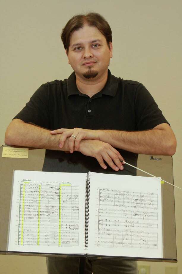 (For the Chronicle/Gary Fountain, May 6, 2014) Hector Aguero, who leads three orchestras. He's the orchestra director at the High School for Performing and Visual Arts; he leads the Houston Youth Symphony's intermediate-level Sinfonia; and he's the music director of the Fort Bend Symphony, a community orchestra for adults. Aguero has been involved in bands and orchestras since he was a sixth-grader in Laredo, his hometown. Photo: Gary Fountain, Freelance / Copyright 2014 by Gary Fountain
