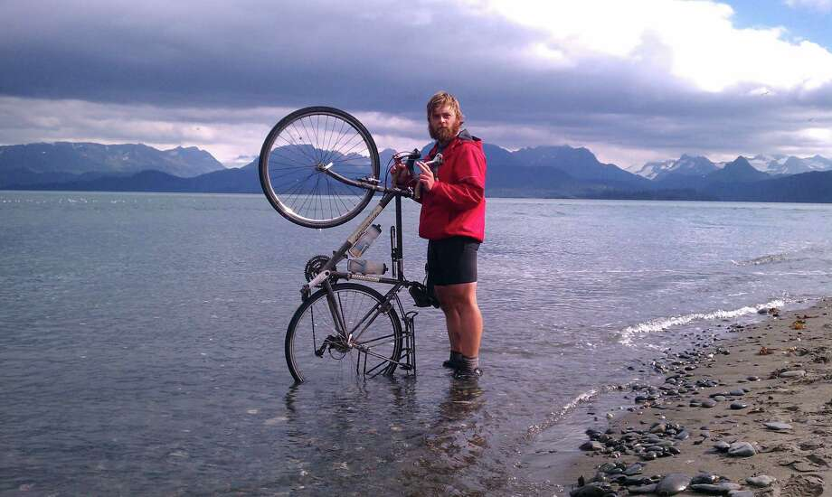 Chandler Wild dipping his tire in the ocean upon reaching the end of the road in Alaska. Location: Homer, Alaska Photo: Scott DelaCruz