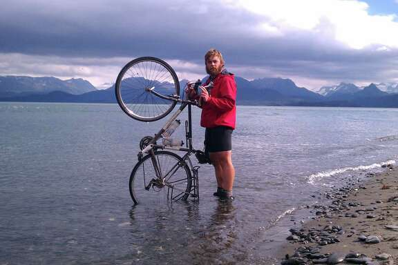 Chandler Wild dips his tire in the ocean upon reaching the end of the road in Alaska.
