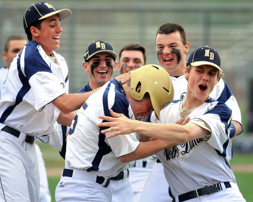 Notre Dame of Fairfield's Brendan Barger, center, is swarmed by teammates after his 7th inning hit drove in the game winning run during a high school baseball game against Bunnell, in Fairfield, Conn. May 12, 2014.