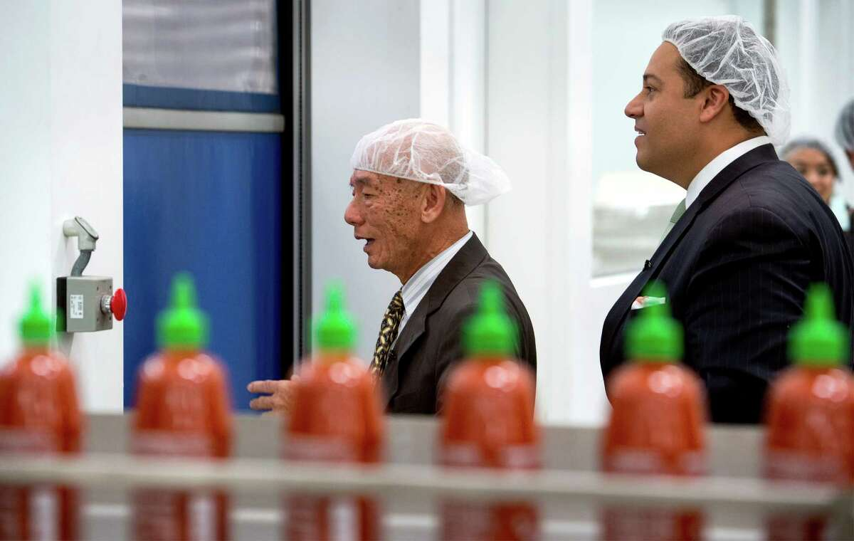 Texas state Rep. Jason Villalba of Dallas, right, on Monday tours the plant of Huy Fong Foods, maker of the Sriracha hot sauce, with founder and CEO David Tran in Irwindale, Calif. A Texas delegation invited Tran to visit the state.