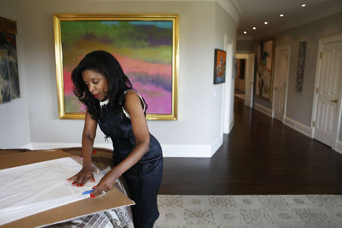 """Pamela Joyner unpacks a new addition to her collection, a print from Carrie Mae Weems' """"The Museum Series,"""" at her home on April 30, 2014 in San Francisco, Calif. In the background is an abstract portrait of Joyner by Richard Mayhew entitled """"Pamela's Aura""""."""