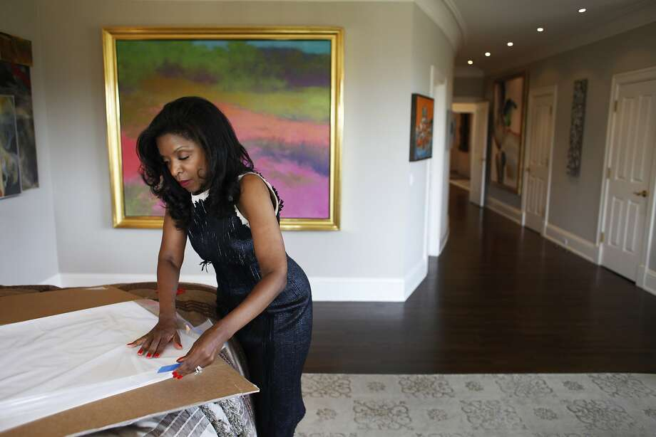 Pamela Joyner unpacks a print from Carrie Mae Weems. Joyner collects art by artists of African descent. Photo: Pete Kiehart, The Chronicle