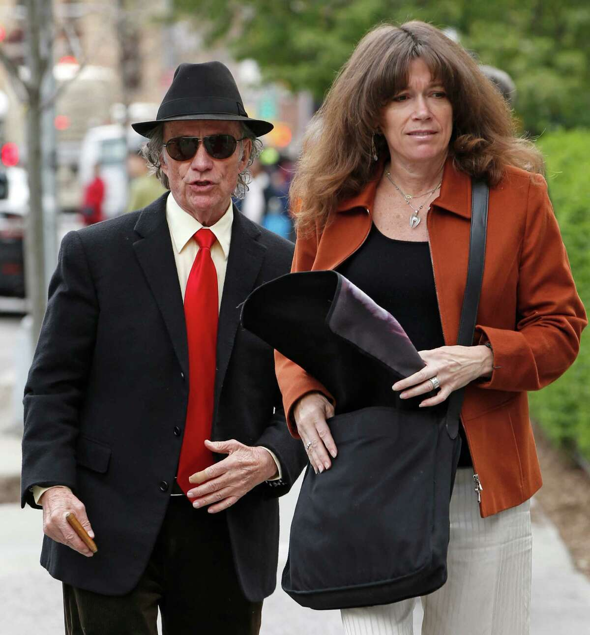 Texas entrepreneur Sam Wyly, left, and his wife, Cheryl, head into U.S. District Court in Manhattan, Tuesday, May 6, 2014, in New York, for closing arguments in the civil trial of Wyly and his late brother Charles. The pair are accused of earning more than $500 million through fraud and deception by secretly trading the securities of public companies they controlled. (AP Photo/Kathy Willens)