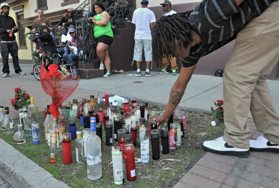 Chaikh Nass of Albany places a lit candle at a memorial Monday afternoon, May 12, 2014, where his friend, 23-year-old Jesse Overton of Albany, was gunned down early Sunday near the intersection of Madison Avenue and South Pearl Street in Albany, N.Y.  (Lori Van Buren / Times Union) Photo: Lori Van Buren / 00026861A