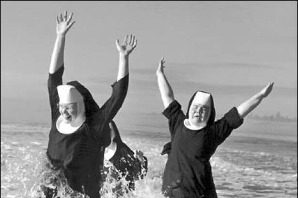 "While ""it's gravity keeps us from drifting lifeless and cold through space"" (as one colleague quipped) ... it's the sun that we worship. Photo: Childlike glee takes flight when a trio of nuns from the Order of St. Benedict make a splash in the Pacific Ocean while vacationing at Grayland in 1960. The photographer was Tom Brownell."