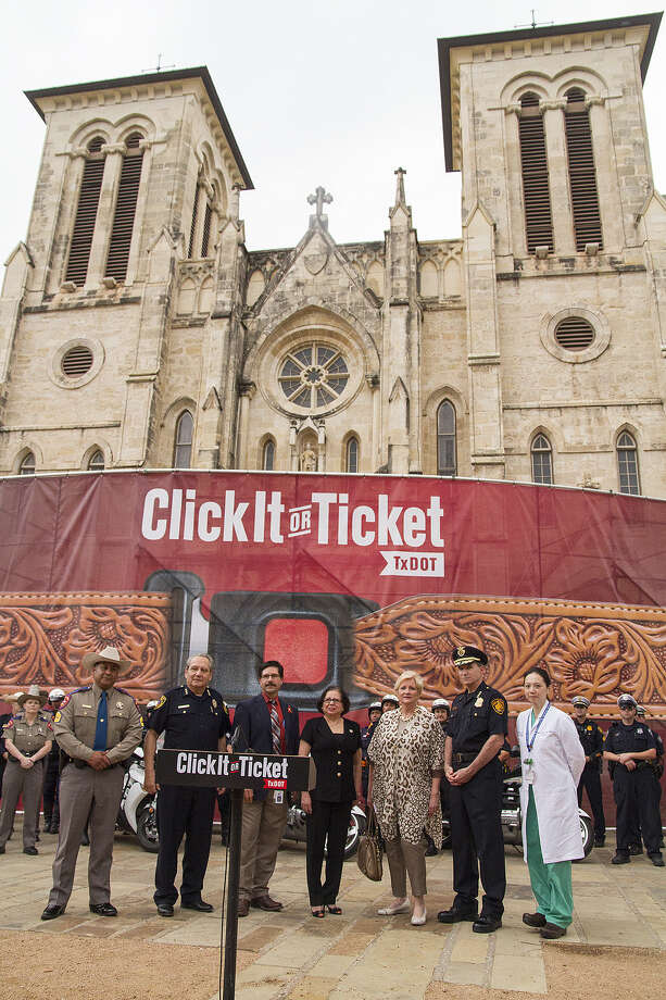 "Speakers at the ""Click it or ticket"" seat belt awareness campaign kickoff stand in front of a western seat belt-themed banner at San Fernando Cathedral. Photo: Alma E. Hernandez / For The San Antonio Express-News"