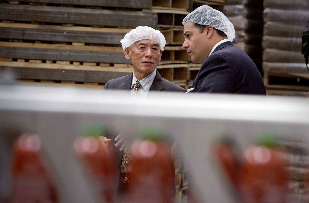 """Huy Fong Foods CEO David Tran talks with Texas Rep. Jason Villalba, leader of the """"Sriracha Delegation"""" during a plant tour."""
