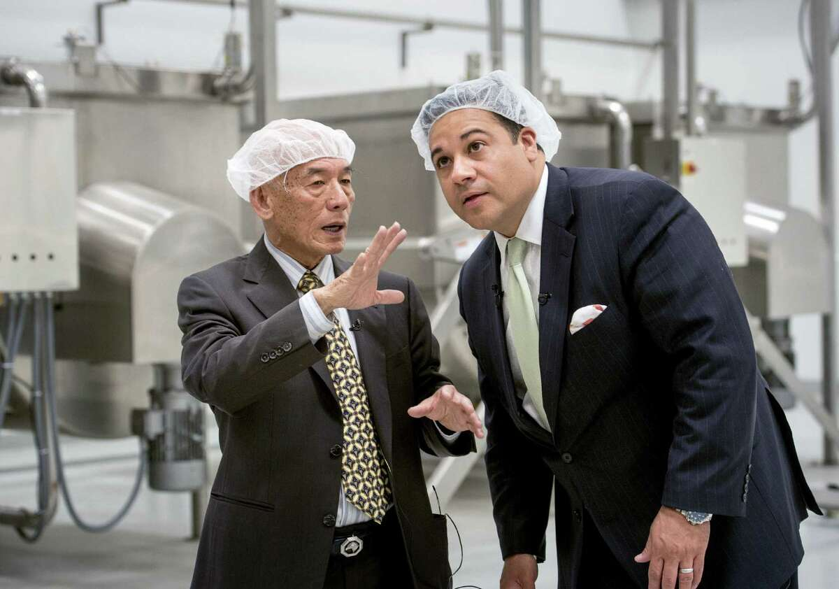 Huy Fong Foods CEO David Tran talks with Texas Rep. Jason Villalba about the making of Sriracha sauce at the plant in Irwindale, Calif. The Texas delegation included State Sen. Carlos Uresti, D-San Antonio.