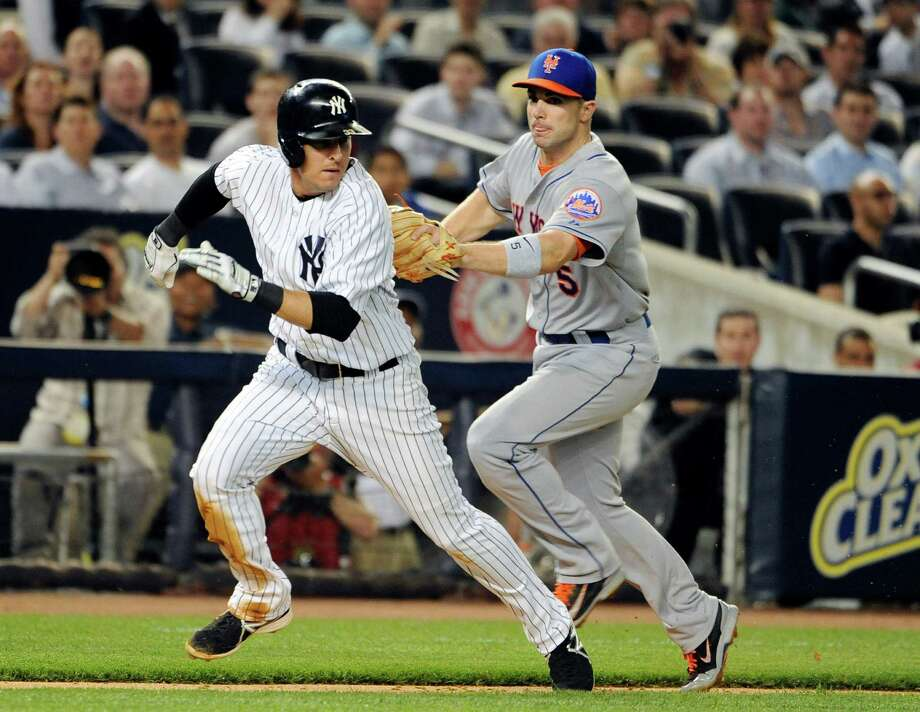 New York Mets third baseman David Wright, right, tags out New York Yankees' Kelly Johnson in a run down between third base and home plate in the sixth inning of an interleague baseball game at Yankee Stadium on Monday, May 12, 2014, in New York. (AP Photo/Kathy Kmonicek) ORG XMIT: NYY124 Photo: Kathy Kmonicek / FR170189 AP