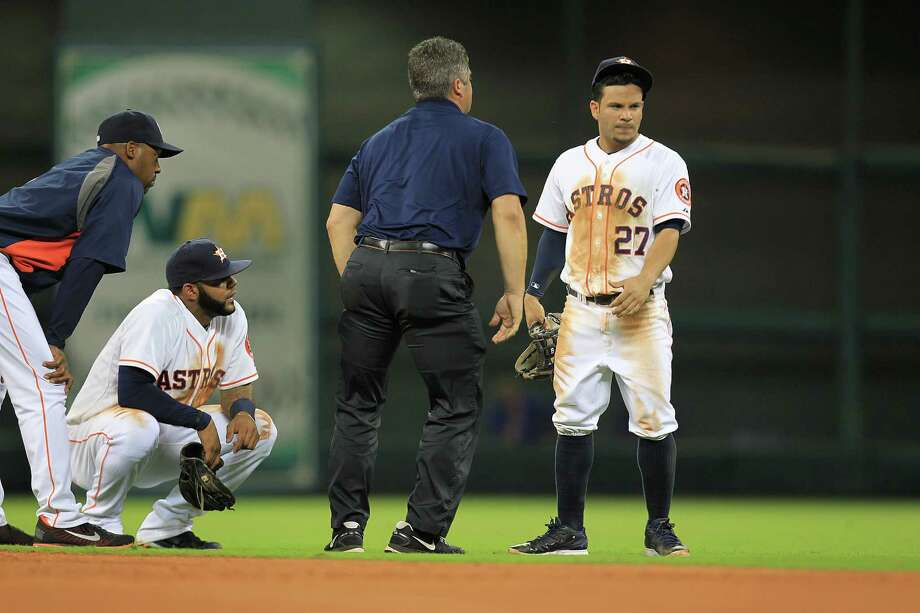 Astros second baseman Jose Altuve dove for a ground ball against tbe Rangers on Monday night, and all he got for his efforts were a dirty uniform and some attention from manager Bo Porter, left, shortstop Jonathan Villar and a trainer. Photo: Mayra Beltran, Staff / © 2014 Houston Chronicle