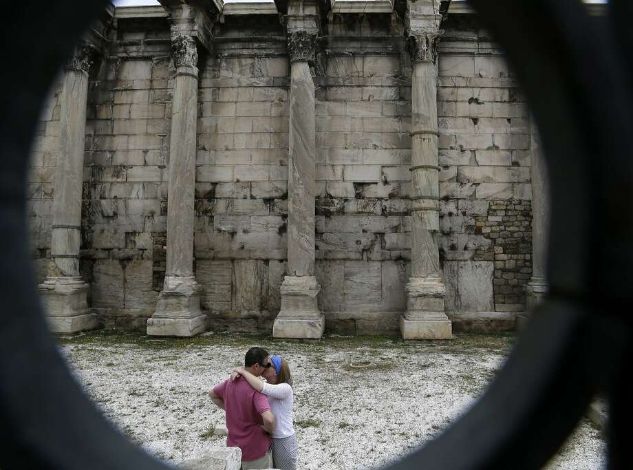 A couple kiss, at the ancient site of Hadrian Library in Athens on Monday, May 12, 2014. Tourism is a major earner in debt-mired Greece, and industry officials say arrivals in the first four months of 2014 are 36.1 percent up compared to a year earlier according to Association of Greek Tourism Enterprises. (AP Photo/Thanassis Stavrakis) Photo: Thanassis Stavrakis, Associated Press
