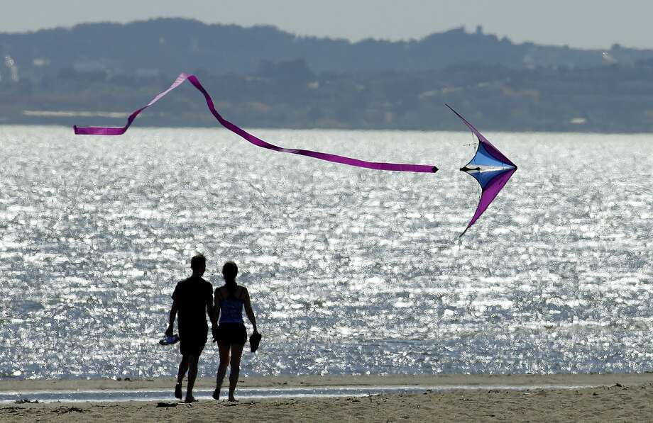 A kite flys past a couple on Crown Memorial Beach Monday, May 12, 2014, in Alameda, Calif. After a hot, windy Mother's Day with temperatures in the mid-80s, a high pressure system was expected to heighten the heat slightly Monday before pushing it to near triple digits in some spots midweek, mostly inland areas already badly parched by drought. High temperatures will extend up and down California, according to the National Weather Service. (AP Photo/Ben Margot) Photo: Ben Margot, Associated Press