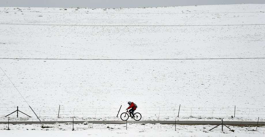 A biker passes fresh snow from the fringe of a major spring snowstorm in the nearby mountains, in Superior, Colo., on Monday, May 12, 2014. A spring storm has brought up to 3 feet of snow to the Rockies and severe thunderstorms and tornadoes to the Midwest. In Colorado, the snow that began falling on Mother's Day caused some power outages as it weighed down newly greening trees. (AP Photo/Brennan Linsley) Photo: Brennan Linsley, Associated Press