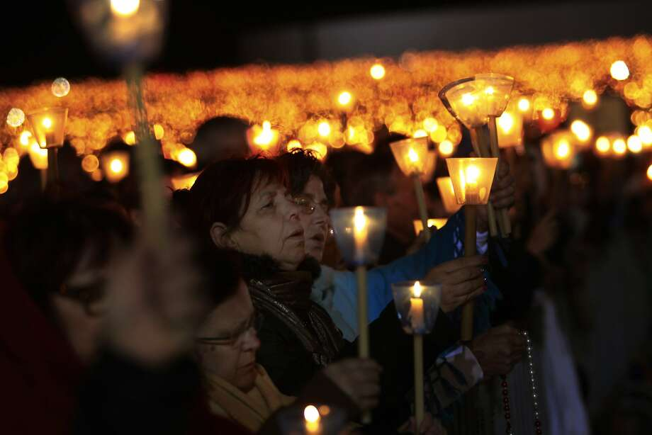 Worshippers pray during a candle light vigil at the Our Lady of Fatima shrine, in Fatima, Portugal, Monday, May 12, 2014. Every year on May 12 and 13 thousands of Catholic pilgrims arrive to Fatima Sanctuary to attend Masses and pray in honor of the Virgin Mary, where it is believed she was witnessed by three shepherd children in 1917. (AP Photo/Francisco Seco) Photo: Francisco Seco, Associated Press