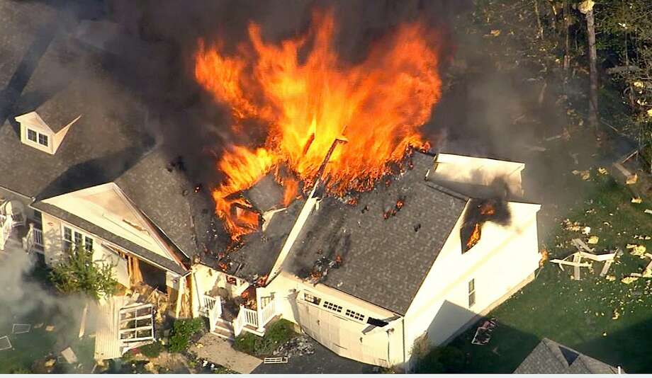 In this frame grab from television helicopter video, a home bursts into flames in Brentwood, N.H., Monday May 12, 2014.  Shots were fired just before the fire, which involved a police officer, according to the New Hampshire State Police. (AP Photo/WHDH-TV 7) TV OUT Photo: Associated Press