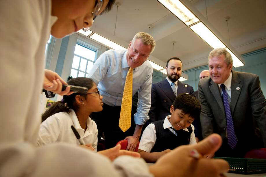 New York Mayor Bill de Blasio, center left,  visits with students in a fourth grade art class at P.S.69 in the Queens borough of New York Monday, May, 12, 2014. He is joined by Assemblyman Francisco Moya, center, and City Councilman Daniel Dromm, right. (AP Photo/Bryan Smith) Photo: Bryan Smith, Associated Press