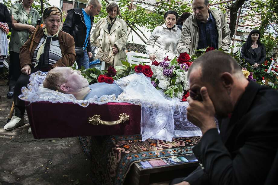 A man cries during the funeral of Alexey Vorobyov, a civilian killed by Ukraine National Guard during an operation against pro Russian activist last Friday in Mariupol, Ukraine, Monday, May 12, 2014.  Pro-Russia insurgents in eastern Ukraine declared independence Monday, a day after holding a hastily arranged referendum vote on separatism that Ukraine's government and its western allies said violated international law. (AP Photo/Manu Brabo) Photo: Manu Brabo, Associated Press