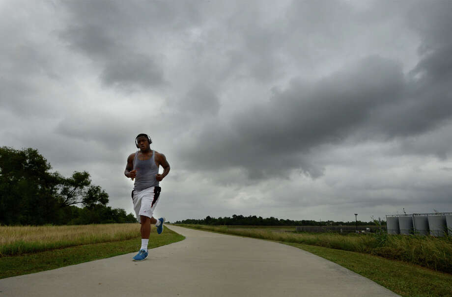 Dark clouds hover overhead as Khadeem Charles runs the Beaumont Hike and Bike trail on Monday, May 12. Guiseppe Barranco/@spotnewsshooter Photo: Guiseppe Barranco, Photo Editor