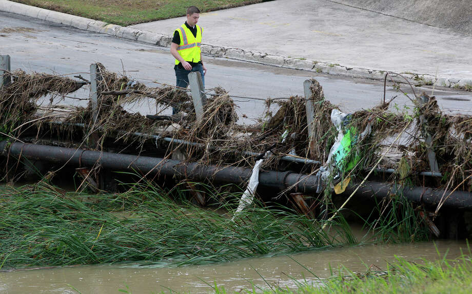 Bjorn Boentges, a project manager for Bexar County Flood Control, walks past debris Tuesday May 13, 2014 stuck in a bridge railing at a low water crossing at Vicar and Perrin Beitel. Heavy rain swept through the San Antonio area causing numerous road closures. Boentges was taking pictures in the area as a reference for future flood control projects. Photo: JOHN DAVENPORT, San Antonio Express-News / ©San Antonio Express-News/John Davenport