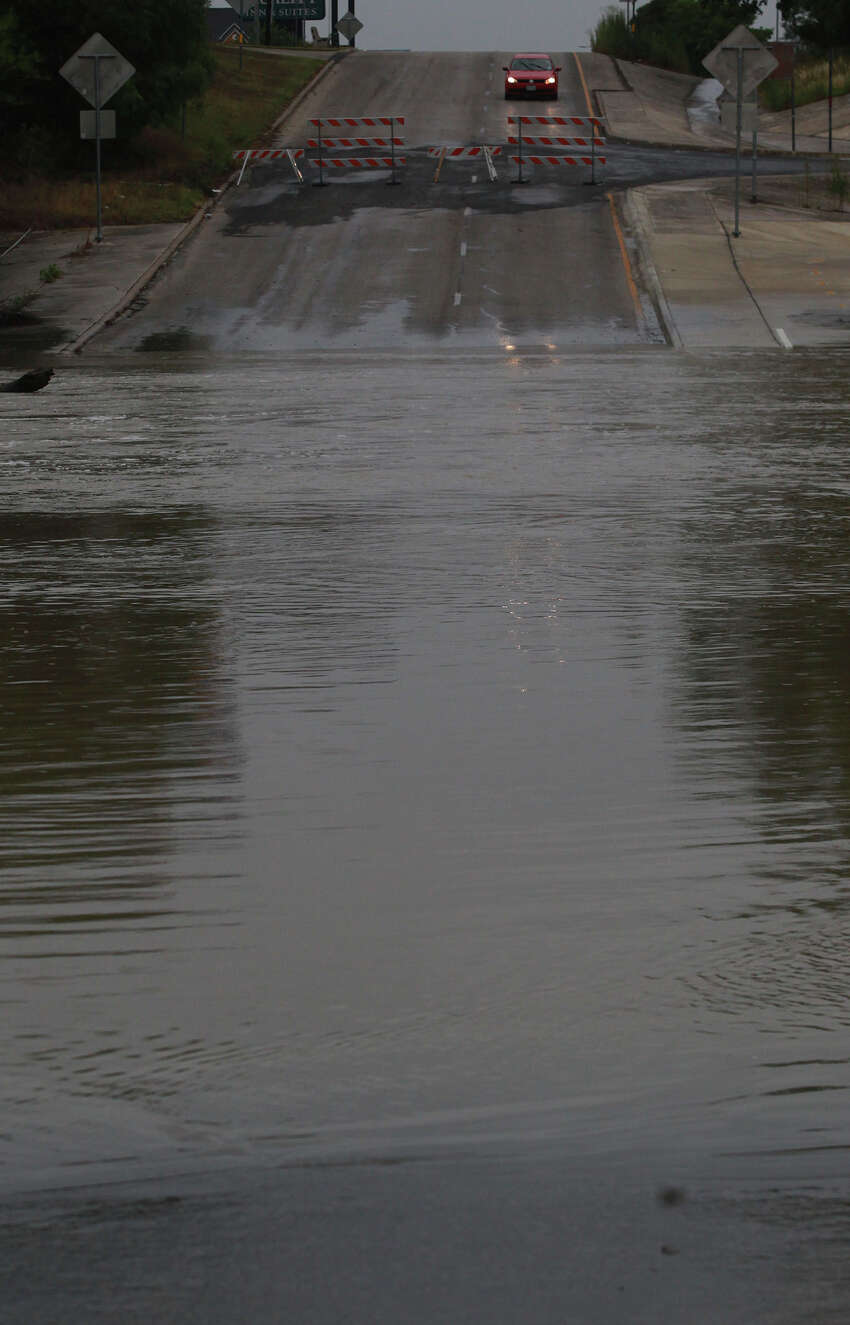 A driver pauses in a car Tuesday May 13, 2014 near debris in the road close to Salado creek and I-35 after flooding took place last night and early this morning. Heavy rain caused many San Antonio roads to be closed last night.
