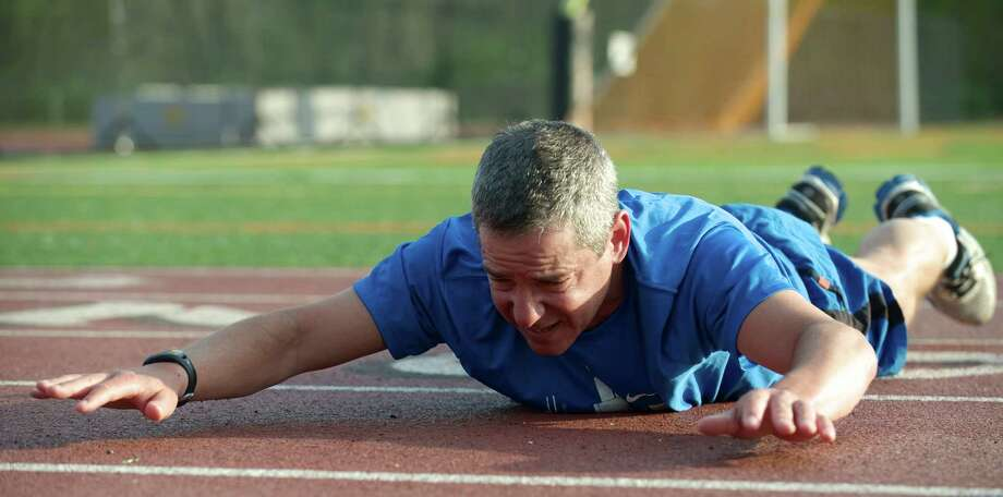 Jim Levy, 50, of Ridgefield, Conn, stretches after finishing his early morning workout on Tuesday, May 13, 2014. Marcus is part of a group that meets twice a week at the Ridgefield High School track to workout. Photo: H John Voorhees III / The News-Times Freelance