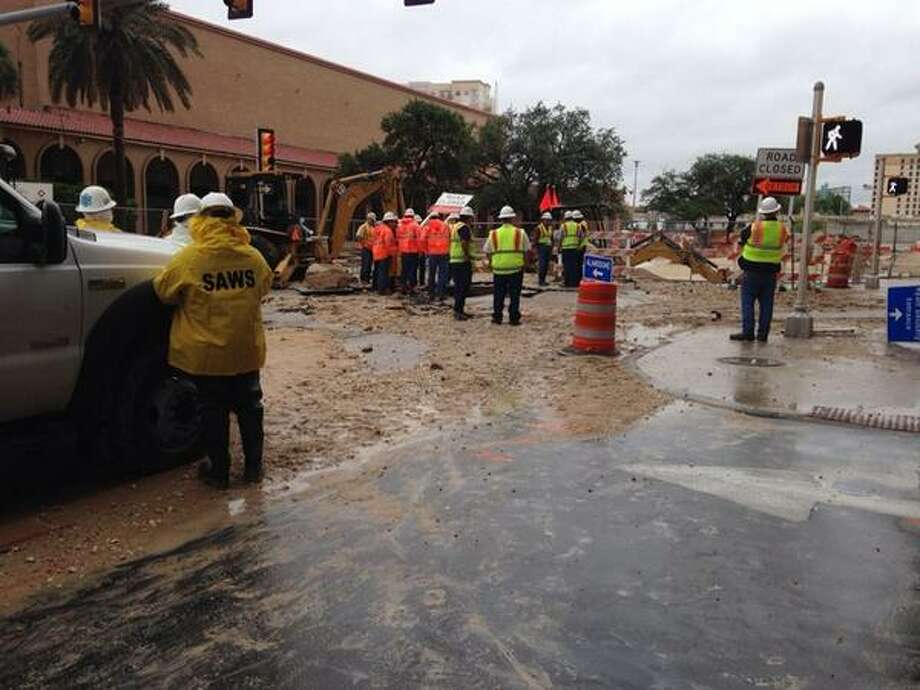 A water line that ruptured is next to a large gas line, and CPS Energy is working to secure the gas line before SAWS crews examine the water main to determine why it broke. Photo: Alia Malik/San Antonio Express-News