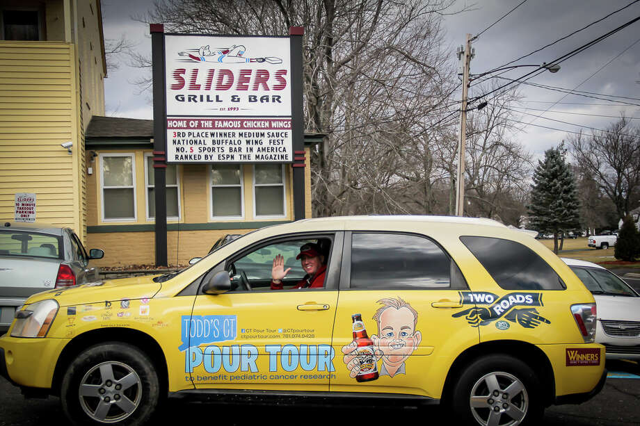 Todd Ruggere leaves a bar in Berlin, Conn., on Jan. 15, 2014, after making the second stop in the state for his Todd's Pour Tour. Ruggere is drinking a beer in all 169 Connecticut towns this year to raise money for the Smilow Cancer Hospital at Yale-New Haven. Photo: Contributed Photo, Contributed / New Canaan News Contributed